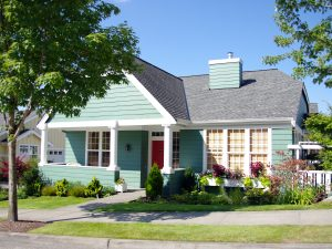 Single family home with pastel green exterior paint and landscaping